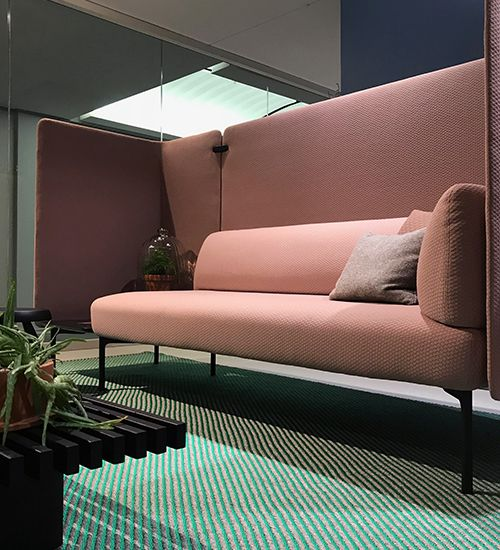 Pale pink sofa with acoustic walls on top of a teal and grey striped rug. Haworth
