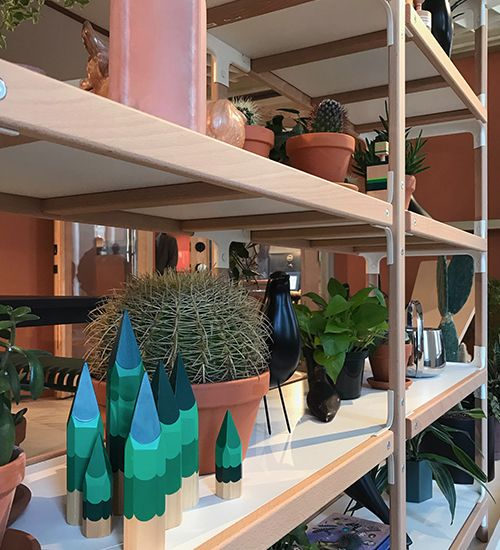 Potted cacti littered among pale pink and blue-green odds and ends on a shelf. Herman Miller