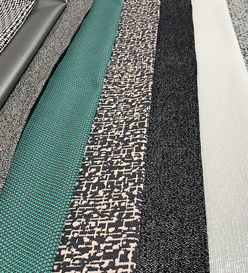 Grey geometric textiles with a pop of teal green laid in a row. Luna Textiles