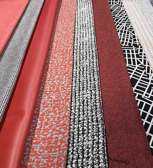 Row of textiles in terra cotta pinks and black-and-white geometrics. Luna Textiles