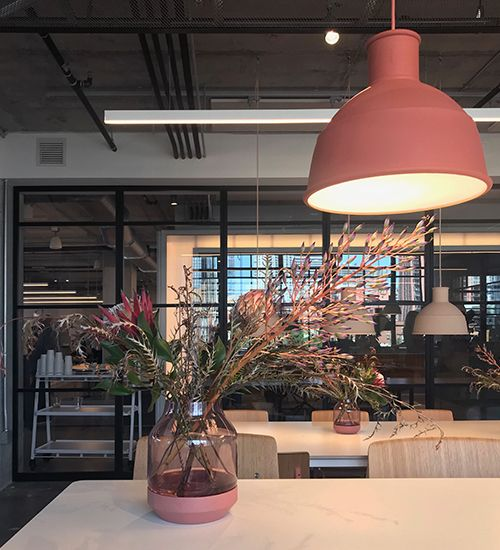 Flower arrangement on a table under a pinky-orange pendant light. Muuto