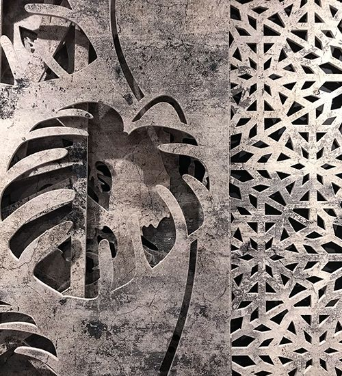 Two fabric panels with concrete texture. The front panel has a bold monstera leaf pattern, while the back panel has a snowflake-like geometric cut-out pattern. Buzzispace