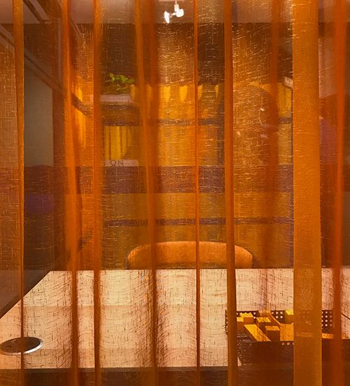 Orange translucent curtain obscuring a workspace with desk and chair. Buzzispace
