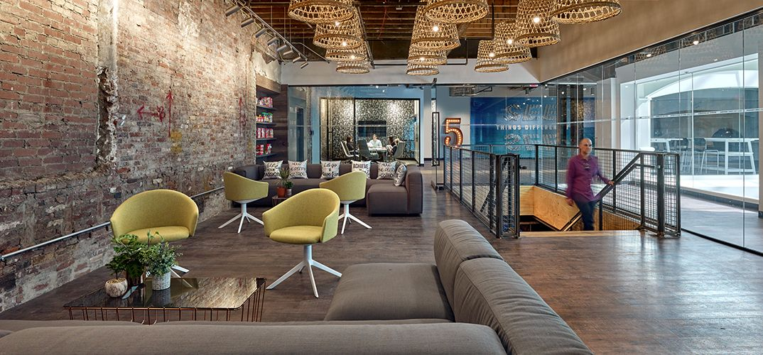 Open workspace with raw brick walls, wood-textured LVT, and plenty of soft textiles to contrast