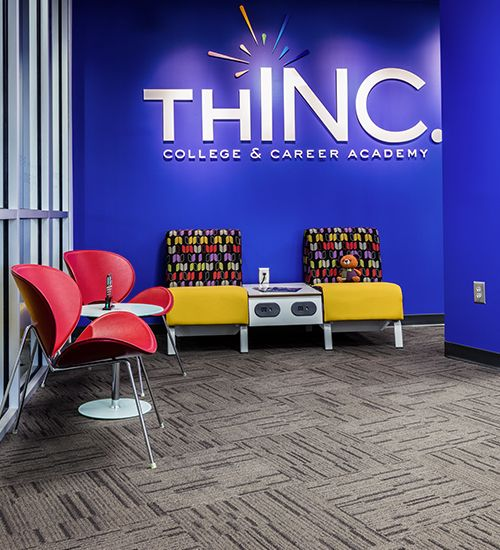 THINC Academy lobby with school logo on a bright blue wall.