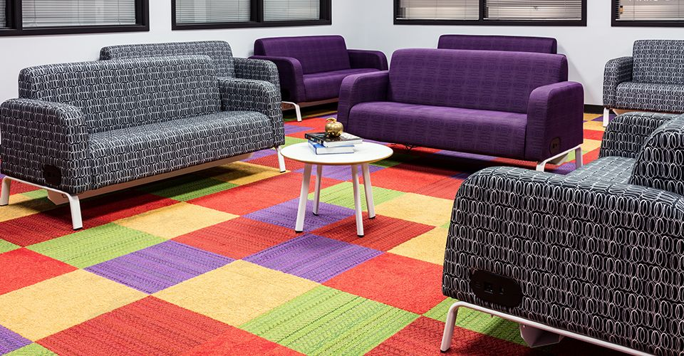 Colorful, flexible learning space with red, yellow, purple, and green carpet tiles.