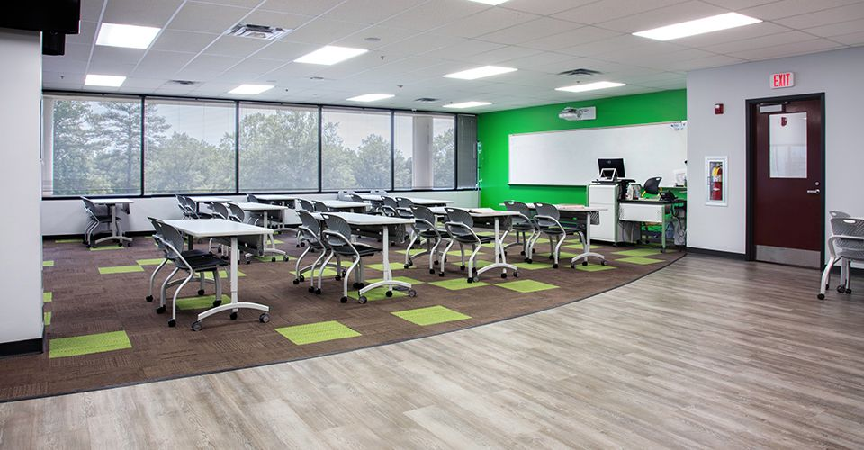 Open classroom space with movable desks, green walls, and brown and green carpet tiles on the floor..
