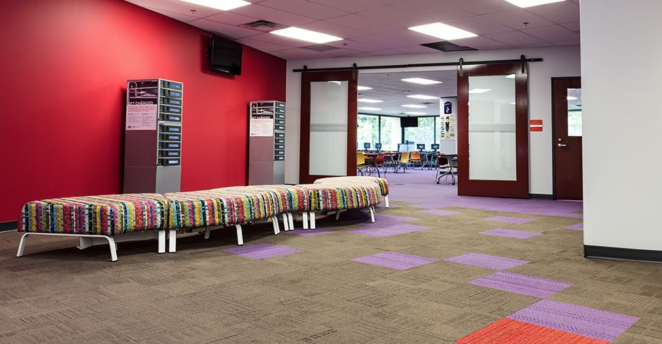 In-between space that has graphic upholstered benches and purple carpet tile that provides wayfinding into a classroom space.