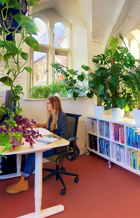 girl sitting at desk in office with plants