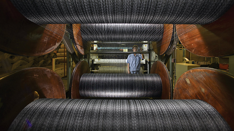 A tufting machine operator watches for irregularities as yarn is pulled from spools.